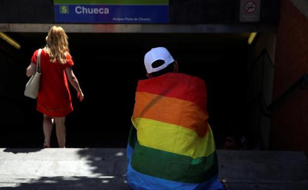 Un hombre ataviado con la bandera LGTB junto al acceso de Metro de Chueca.