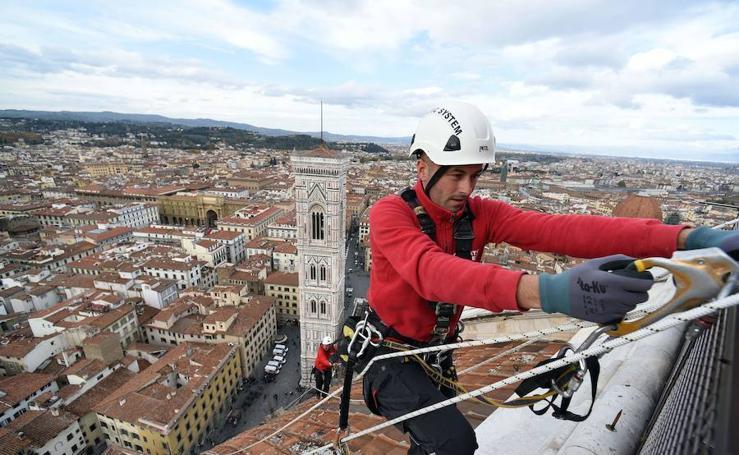 Dos alpinistas examinan el estado de la cúpula de la Catedral de Santa María del Fiore, en Florencia