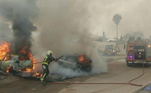 Arden dos vehículos estacionados en un aparcamiento del centro de Nerja
