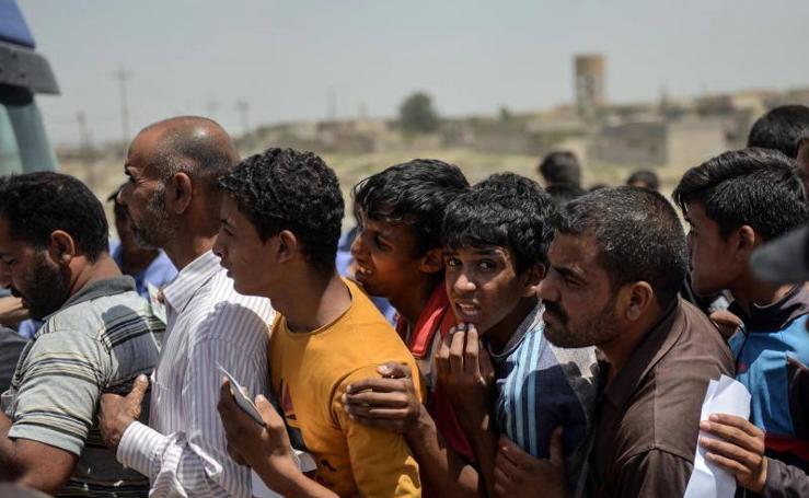 Ciudadanos iraquíes esperan para recibir comida