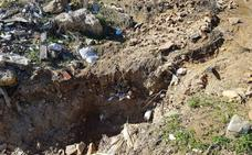 Las lluvias reabren el antiguo vertedero y arrastran basura a la carretera en Carratraca