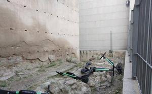 Tiran sobre la muralla medieval de calle Carretería cuatro patinetes eléctricos
