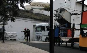 Un camión se queda atascado en la fachada de una harinera en Coín