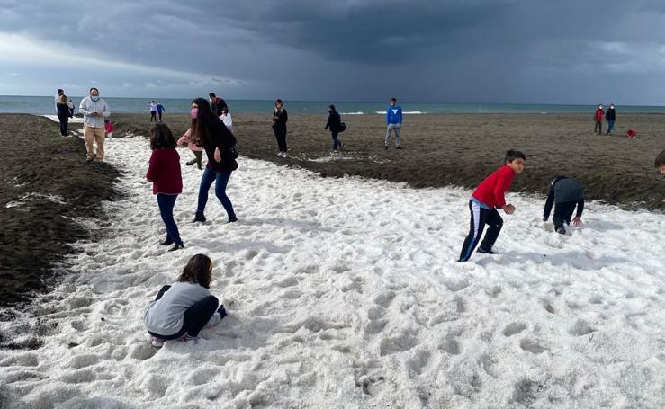 Insólita imagen de la playa de Benajarafe tras la fuerte granizada de esta mañana